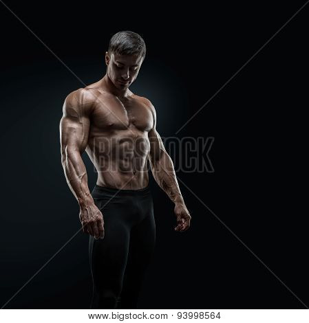 Fit Young Bodybuilder Posing Over Black Background