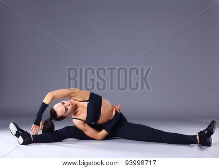 Young attractive female fitness woman performing a twine .