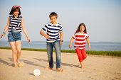 stock photo of brother sister  - Brother and sisters play with a beach ball outdoors - JPG