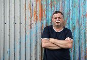 picture of 55-60 years old  - Mature mustachioed man sitting against the wall - JPG