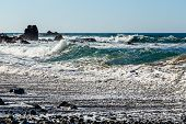image of atlantic ocean  - Waves and foam on wild stone beach on coast of the Atlantic ocean with sky and rock on skyline or horizon in Tenerife Canary island Spain at spring or summer - JPG