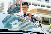 stock photo of key  - Young adult chinese businessman holds keys of new car leaning on auto door - JPG