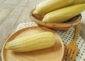 stock photo of corn  - Corn and sticky corn placed on a wooden table - JPG