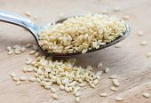 picture of sesame seed  - A spoon with white sesam seeds on the wooden background - JPG