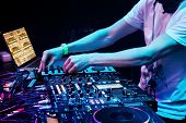 stock photo of foreground  - Dj mixes the track in the nightclub at party - JPG