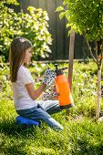 pic of fertilizer  - Young brunette girl working in garden with fertilizing spray - JPG