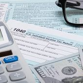 pic of cpa  - US 1040 Tax Form calculator glasses and dollars  - JPG