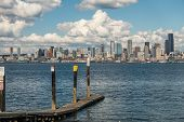 picture of puffy  - White puffy clouds hover over the Seattle skyline on a sunny day - JPG