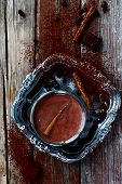 foto of cinnamon sticks  - Top view of hot chocolate cocoa with cinnamon sticks on vintage wooden background - JPG