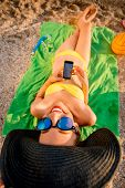 stock photo of crazy hat  - Young funny woman in swimsuit reading with mobile phone lying on the green towel on the beach - JPG
