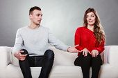 pic of shy girl  - Shy woman and man sitting on sofa couch next each other - JPG