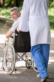 picture of male nurses  - Male nurse pushing a senior patient in wheelchair outdoor on a sunny day - JPG
