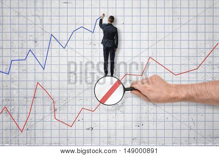 Back view of businessman drawing a blue diagram above the red one. Setting and achieving goals. Earnings growth. Increase in income.