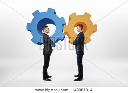Two businessmen standing opposite to each other with cartoon cogwheel. Interaction and cooperation. Staff. Togetherness. Partnership. Teamwork.
