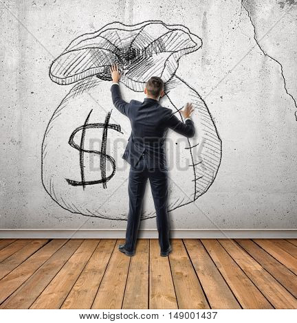 Back view of businessman touches a sketch of money bag on concrete wall. Setting and achieving goals. Desire and dream. The obsession with the money.