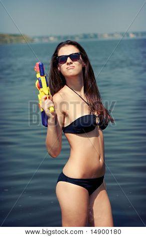Pretty Young Women Playing Water Gun At The Beach