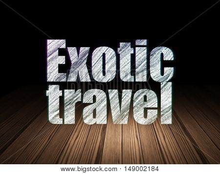 Tourism concept: Glowing text Exotic Travel in grunge dark room with Wooden Floor, black background