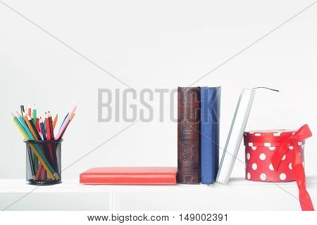 Pot with colorful colored pencils red blue diaries brown book and beautiful round red present box on shelf isolated on white background copy space
