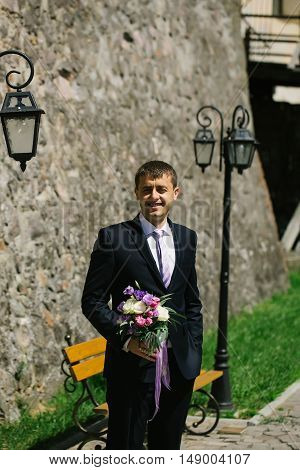 Handsome groom man in elegant suit stands with wedding bouquet on masonry wall