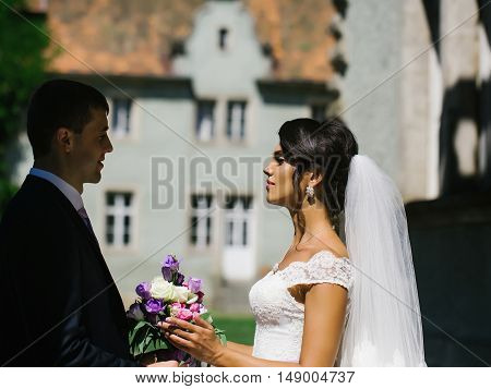 Beautiful bride woman and elegant groom man with wedding bouquet look at each other with love outdoors on sunny day