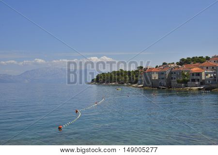 Clear water in foreground and blue sky and some house in Postira village on Brac island in Croatia.