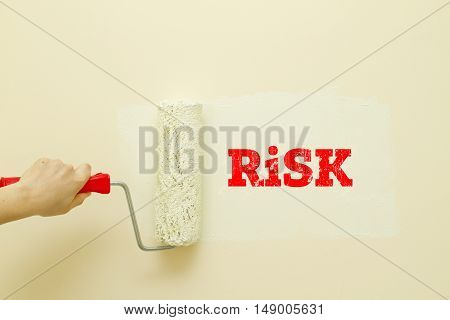 Woman hand painting wall written Risk on it.