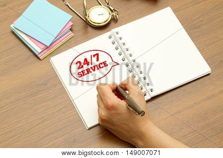Hand writing 24/7 service on a notebook with pen.