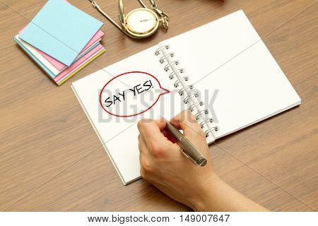 Hand writing SAY YES word on a notebook with pen.