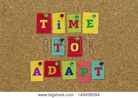 TIME TO ADAPT message written on colorful sticky notes pinned on cork board.