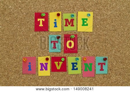 TIME TO INVENT message written on colorful sticky notes pinned on cork board.