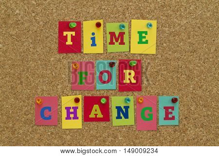 TIME FOR CHANGE message written on colorful sticky notes pinned on cork board.
