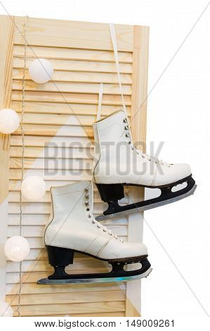 pair of feminine figure skates hanging on laces on wooden or wood door with snowballs decoration in winter christmas or new year holidays isolated on white background