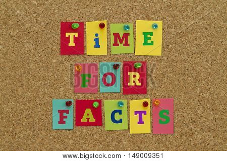 TIME FOR FACTS message written on colorful sticky notes pinned on cork board.
