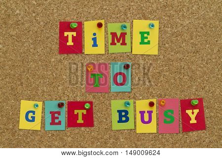 TIME TO GET BUSY message written on colorful sticky notes pinned on cork board.