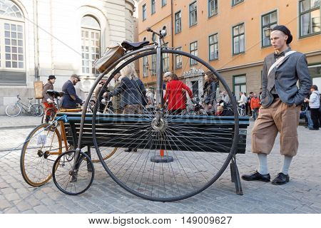 STOCKHOLM - SEPT 24 2016: Closeup of a parked very old high wheeler bicycle and a boy watching it in the Bike in Tweed event September 24 2016 in Stockholm Sweden