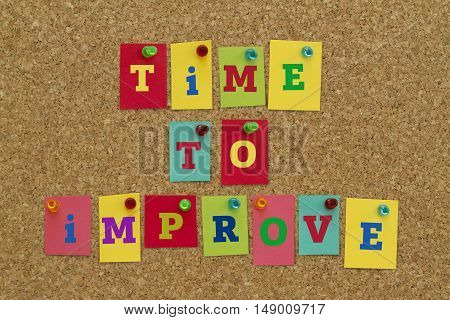 TIME TO IMPROVE message written on colorful sticky notes pinned on cork board.