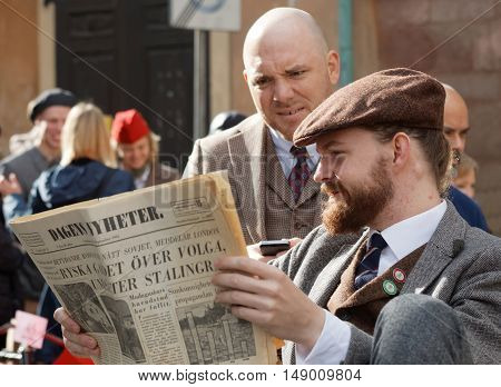 STOCKHOLM - SEPT 24 2016: Two men reading vintage newspaper wearing old fashioned tweed clothes in the Bike in Tweed event September 24 2016 in Stockholm Sweden