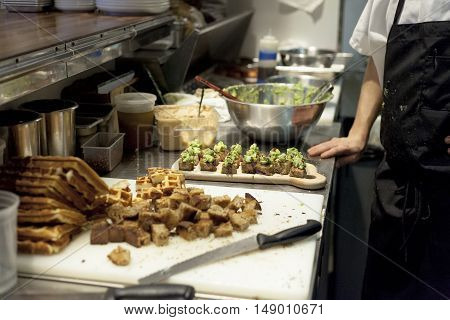 A chef rests before finishing appetizers for restaurant guests.