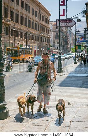 A man runs along the street with three dogs, July 27th 2016 Palermo, Sicily, ITAALIA