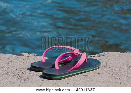 flip-flops on the beach near the water in summer