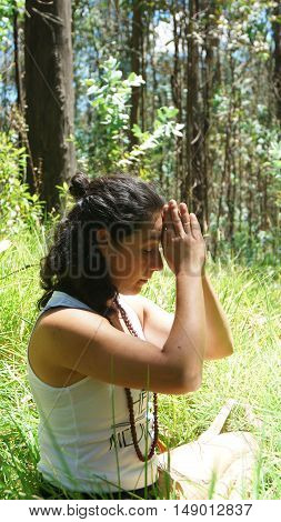 Young latin woman doing yoga in the woods