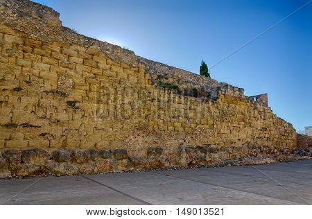 Ruins of sandstone roman wall in Tarragona, summer Spain