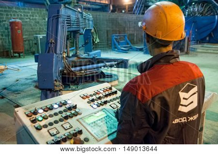 Tyumen, Russia - August 13, 2013: Circle pit making department at construction material factory ZHBI-5. Concrete Goods Plant No. 5. Worker control process of making circle concrete block