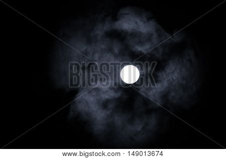Shining full moon in the night sky and dramatic night clouds -night mysterious landscape in cold tones. Night sky gothic background with full moon beneath the clouds.