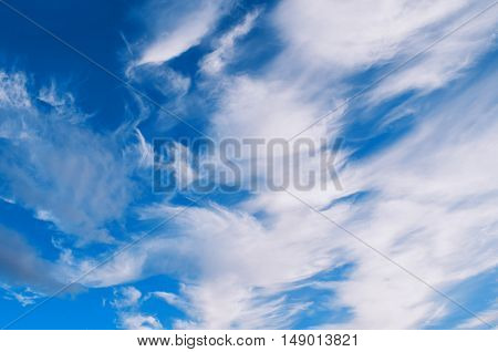 Sky landscape of cloudy sunset sky. Blue sky background with white clouds lit by sunny light in good weather- natural sky background. Colorful sky. Beautiful clouds in the sky lit by sunlight