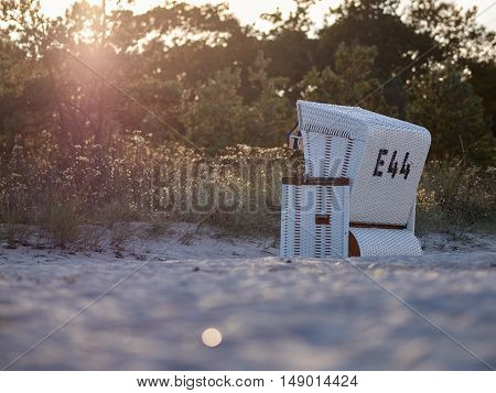 The evening sun adds some romantic light to a roofed wicker beach chair