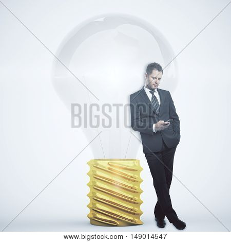 Businessman using smartphone while leaning on abstract lightbulb. Idea concept. 3D Rendering