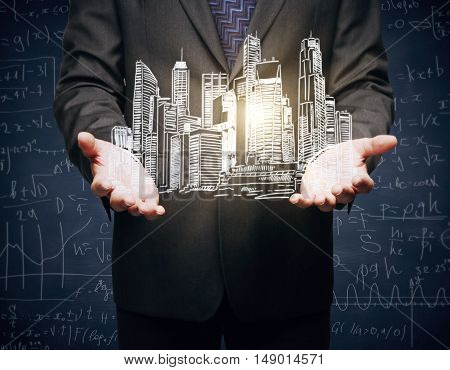 Closeup of businessman hands holding abstract illuminated city sketch on dark background with mathematical formulas