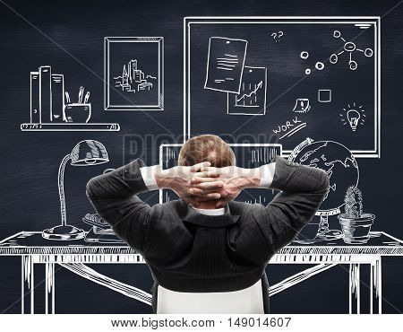 Back view of young businessperson in suit relaxing in creative drawn office on chalkboard background