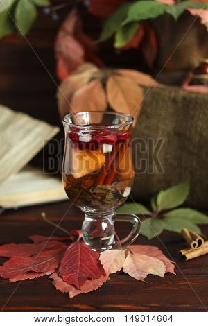 Autumn hot tea with lemon spices in glass cup falling leaves around and old book autumn concept